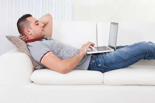 Man Using Laptop While Lying On Sofa Stock photo © AndreyPopov