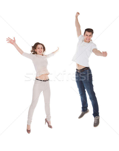Couple In Casuals Jumping Over White Background Stock photo © AndreyPopov