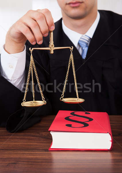Stock photo: Judge Holding Weight Scale In Courtroom
