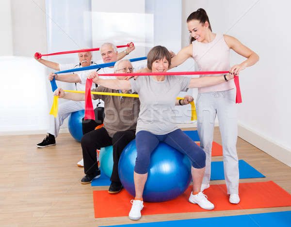 Trainer Assisting Senior People At Gym Stock photo © AndreyPopov