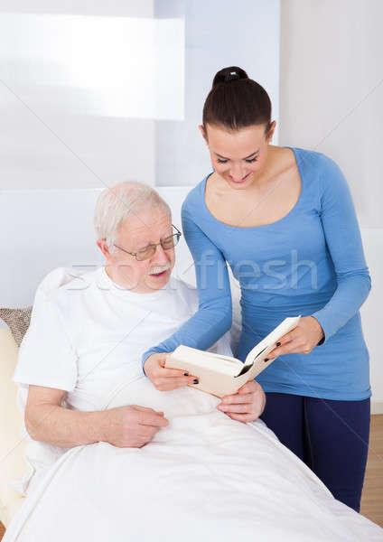 Caretaker And Senior Man Reading Book Stock photo © AndreyPopov