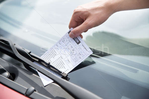 Officer's Hand Putting Parking Ticket On Car Stock photo © AndreyPopov