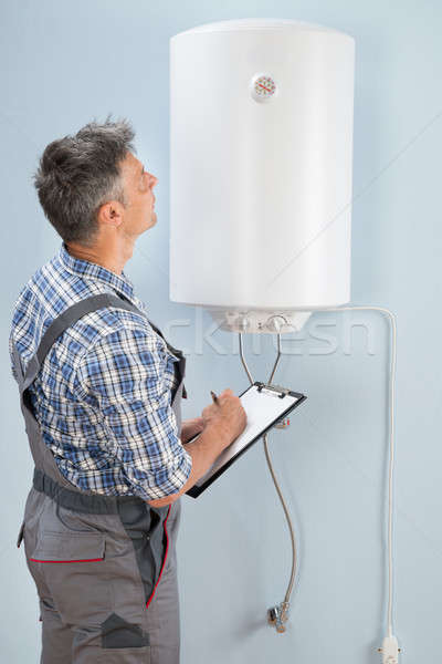 Male Plumber With Clipboard Looking At Electric Boiler Stock photo © AndreyPopov