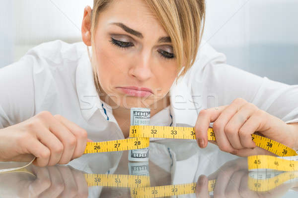 Unhappy Businesswoman With Measuring Tape And Banknote Stock photo © AndreyPopov