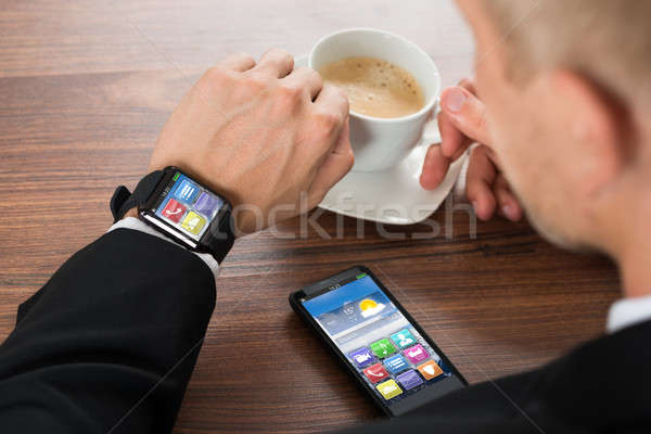 Businessman With Smartphone And Smartwatch Drinking Coffee Stock photo © AndreyPopov