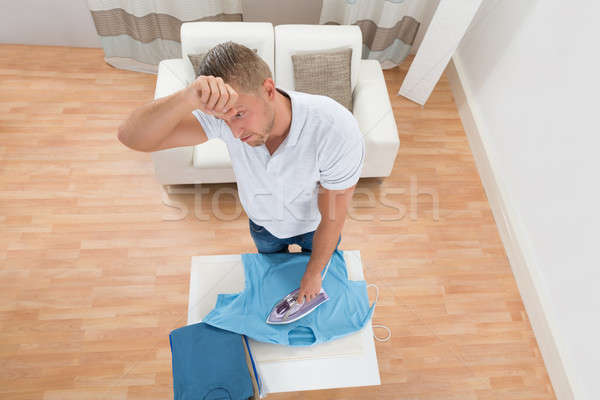 Tired Man Ironing Clothes Stock photo © AndreyPopov