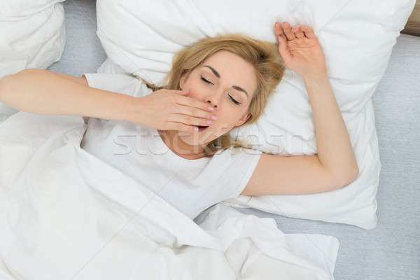 Woman Yawning In Bedroom Stock photo © AndreyPopov