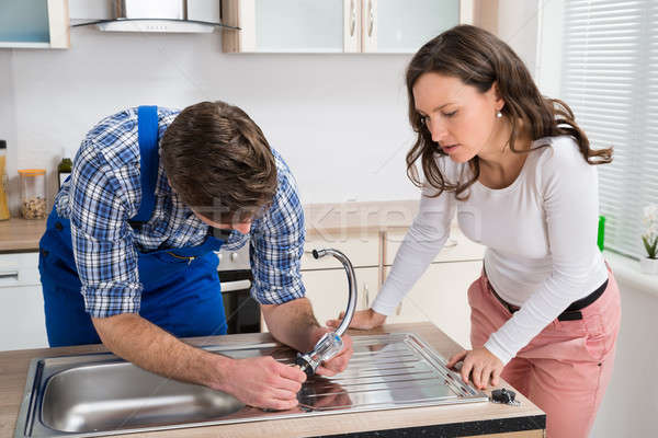 Woman Looking At Plumber Fixing Steel Tap Stock photo © AndreyPopov