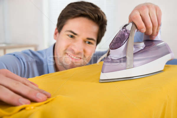 Young Man Ironing T-shirt With Electric Iron Stock photo © AndreyPopov