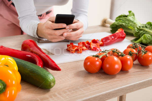 Woman With Mobile Phone And Vegetables Stock photo © AndreyPopov