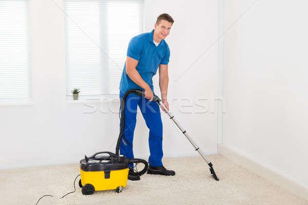 Woźny czyszczenia dywan szczęśliwy mężczyzna odkurzacz Zdjęcia stock © AndreyPopov