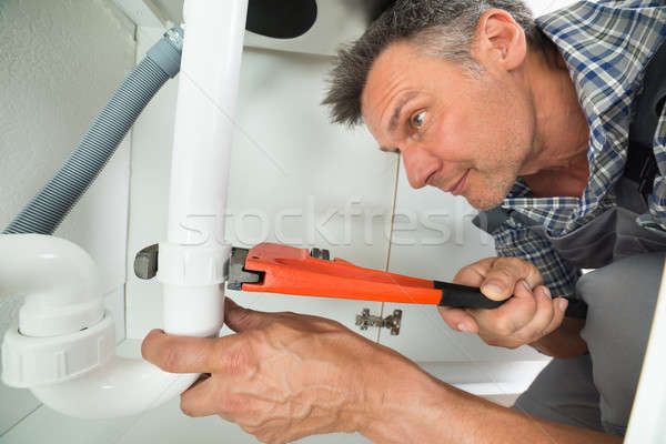 Serviceman Fixing Sink Pipe In Kitchen Stock photo © AndreyPopov