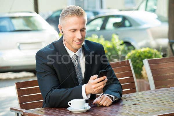 Stockfoto: Zakenman · luisteren · muziek · vergadering · bank · mobieltje