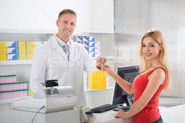 Uśmiechnięty farmaceuta klienta kobiet Licznik sklepu Zdjęcia stock © AndreyPopov