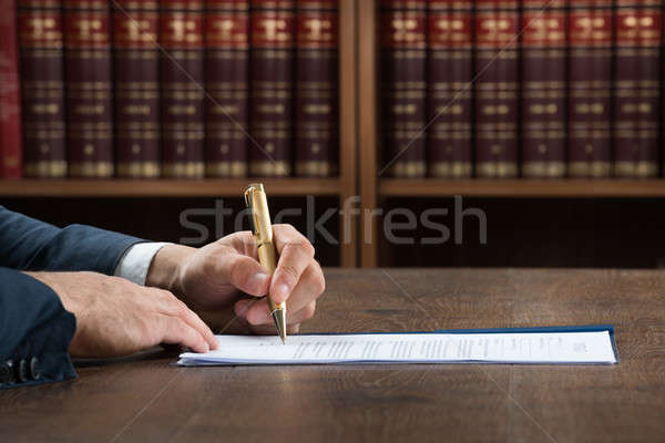 Lawyer Writing On Legal Documents At Desk Stock photo © AndreyPopov