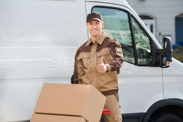 Confident Delivery Man Pushing Parcels On Handtruck Stock photo © AndreyPopov