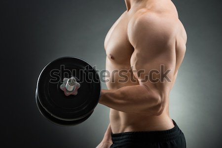 Midsection Of Muscular Man Lifting Dumbbell Stock photo © AndreyPopov