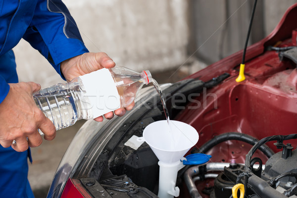 Worker Pouring Water Into Windshield Water Tank Stock photo © AndreyPopov