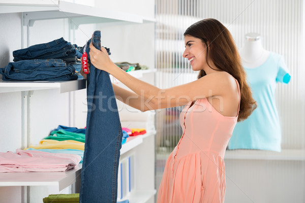 Woman Choosing Jeans In Store Stock photo © AndreyPopov
