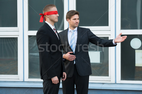 Businessman Assisting Blindfolded Partner Stock photo © AndreyPopov