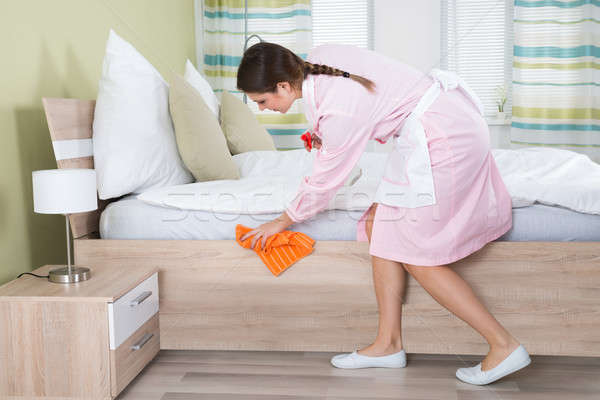 Vrouwelijke huishoudster schoonmaken bed jonge hotelkamer Stockfoto © AndreyPopov