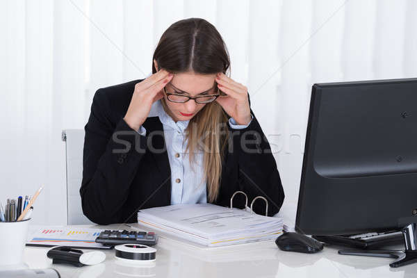 Stressed Businesswoman Sitting At Desk With Financial Report Stock photo © AndreyPopov