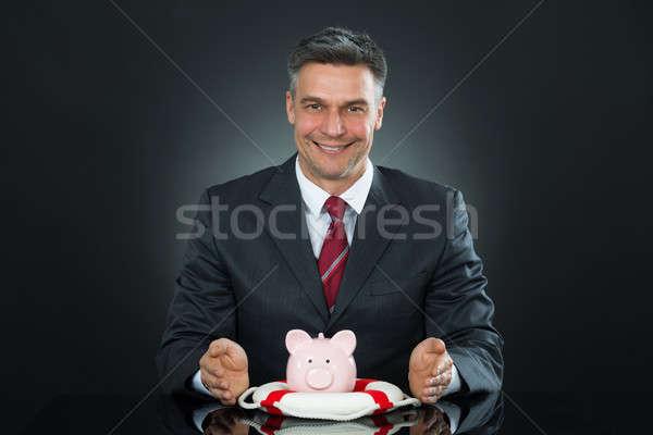 Mature Businessman Protecting Piggybank With Lifebelt Stock photo © AndreyPopov