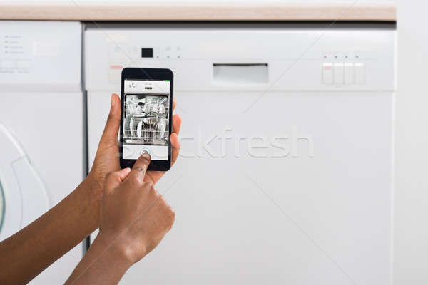 Woman's Hand Using Mobile Phone For Operating Dishwasher Stock photo © AndreyPopov