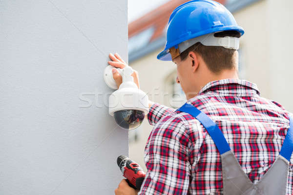 Young Male Technician Installing Camera On Wall Stock photo © AndreyPopov
