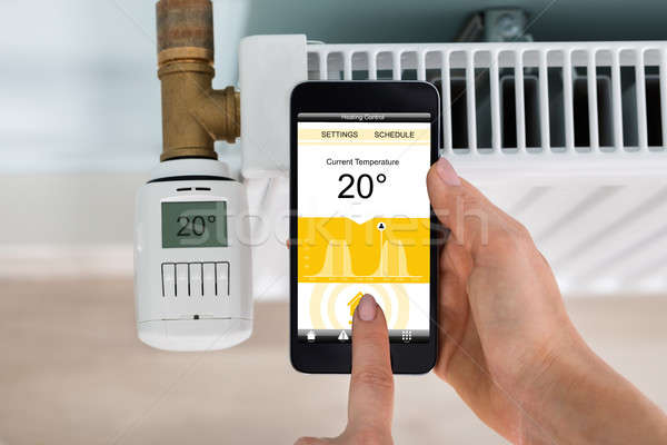Person Setting Temperature Of Thermostat Using Mobilephone Stock photo © AndreyPopov