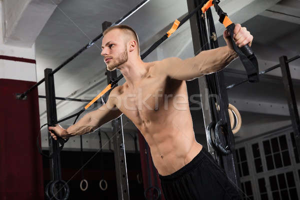 Man Exercising With Suspension Trainer Stock photo © AndreyPopov