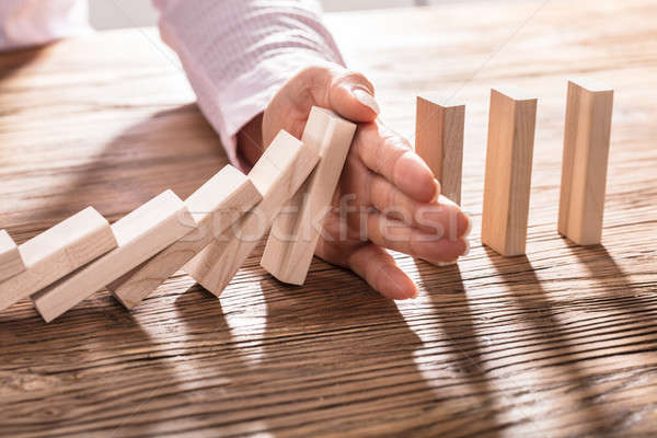 Business Woman's Hand Stopping Falling Blocks On Table Stock photo © AndreyPopov