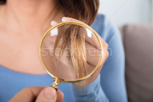 Woman Looking At Her Hair Through Magnifying Glass Stock photo © AndreyPopov