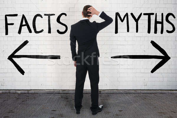Businessman Looking At Arrow Signs Below Facts And Myths Stock photo © AndreyPopov