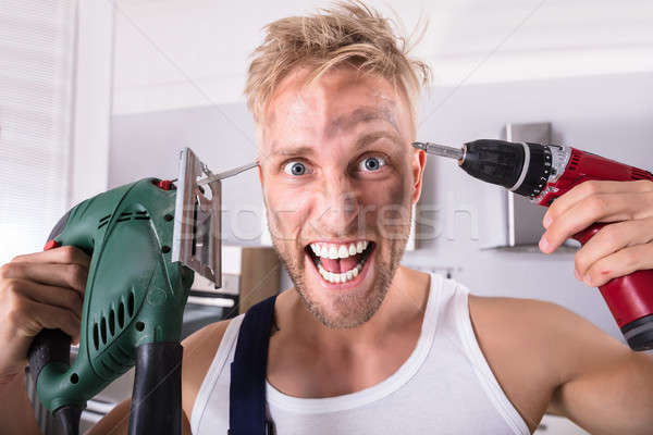 Technician Holding Electric Drill And Screwdriver On His Head Stock photo © AndreyPopov