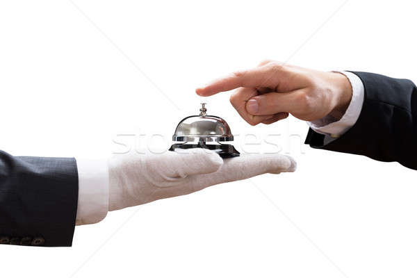 Person's Hand Ringing Service Bell Held By Waiter Stock photo © AndreyPopov