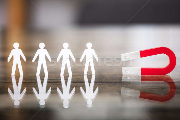 Stock photo: Magnet Attracting Paper Cut Out Standing In Row
