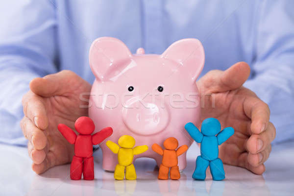 Hand Protecting The Piggybank With Colorful Family Stock photo © AndreyPopov