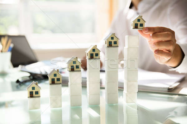 Increasing house models on reflective desk Stock photo © AndreyPopov