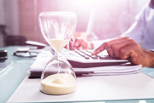 Hourglass In Front Of Businessperson Calculating Invoice Stock photo © AndreyPopov