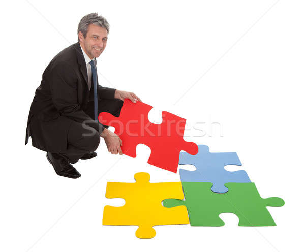 Senior businessman assembling a jigsaw puzzle Stock photo © AndreyPopov