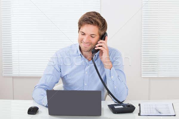 Businessman Communicating On Landline Phone Stock photo © AndreyPopov
