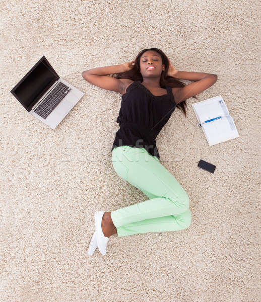 Young African American woman relaxing on rug at home Stock photo © AndreyPopov
