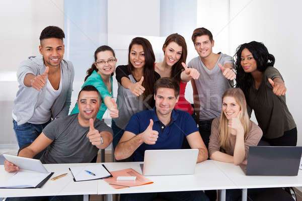 College Students Gesturing Thumbs Up Sign Together Stock photo © AndreyPopov