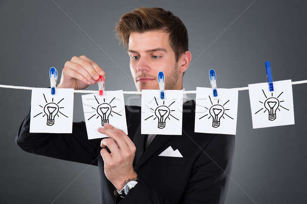 Businessman Pinning Papers Lightbulbs On Clothesline Stock photo © AndreyPopov