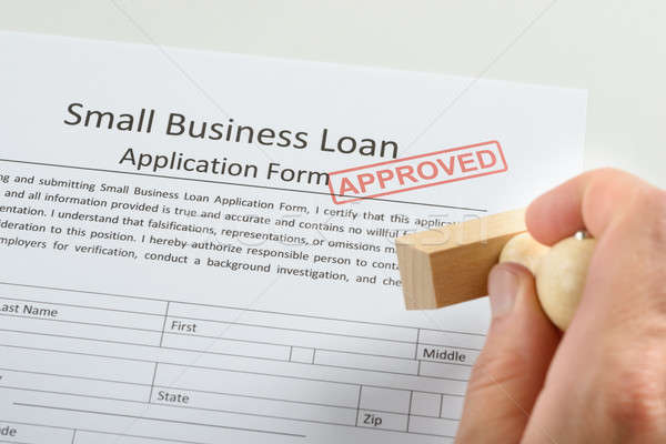 Person Hand Holding Rubber Stamp Over Loan Application Stock photo © AndreyPopov