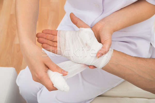 Female Doctor Bandaging Patient's Hand Stock photo © AndreyPopov