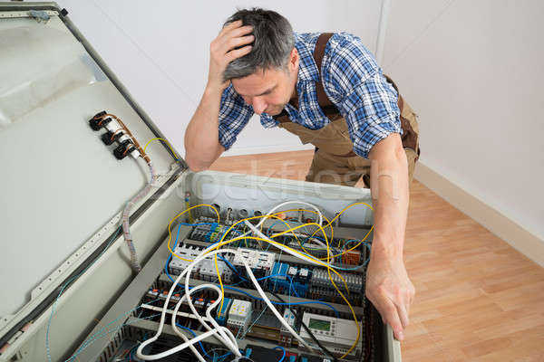 Confused Electrician Looking At Fuse Box Stock photo © AndreyPopov