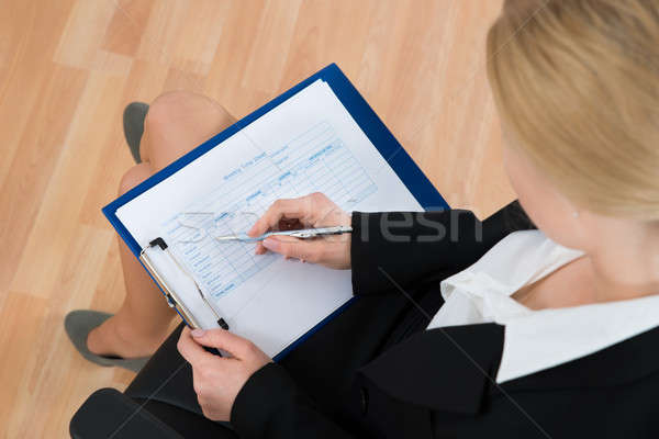 Businesswoman Filling Weekly Time Sheet Stock photo © AndreyPopov