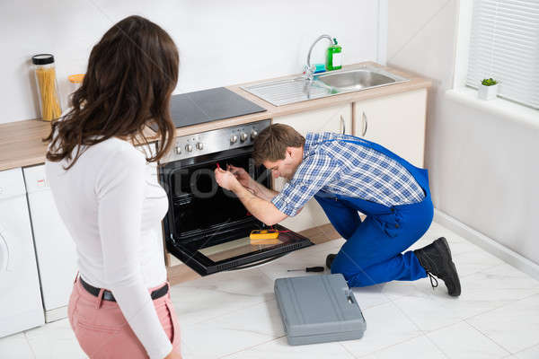 Woman Looking At Worker Repairing Oven Stock photo © AndreyPopov